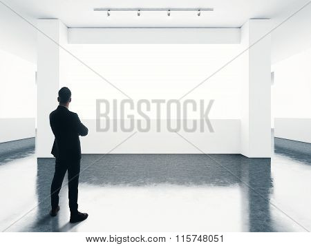 Man wearing suit looking at empty screen in contemporary gallery.