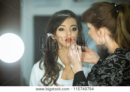 Professional expert, makeup artist prepares very beautiful, young, well-known, glamorous, stunning model for filming shooting for cover of fashion magazine VOGUE, does make-up, makes up lips, art, eyes, white.