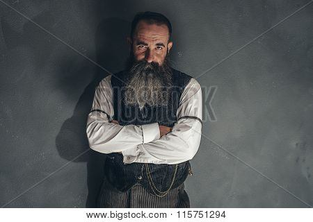 Vintage Bearded Man In 1900 Style Fashion Against Grey Wall.