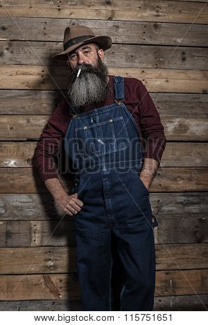 Smoking Vintage Worker Man With Long Gray Beard In Jeans Dungarees. Standing Against Wooden Wall.