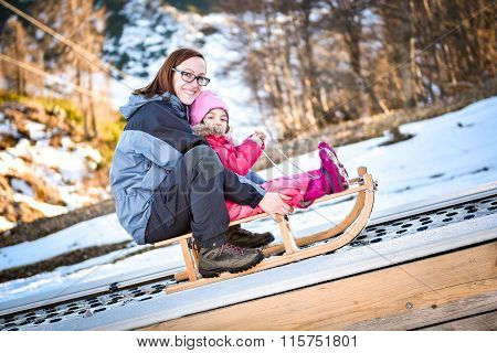 Mother And Little Child On A Ski Conveyor On Sledge