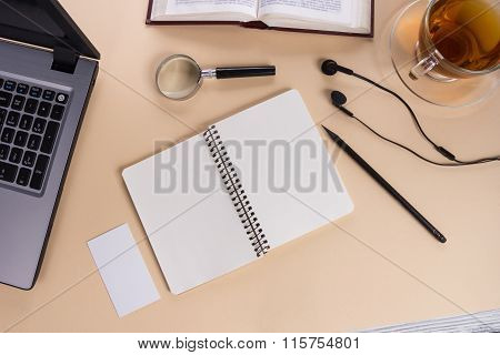 Office table desk with supplies, white blank note pad, cup, pen, pc, crumpled paper, flower on woode