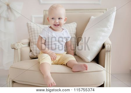 baby one year old sitting in a chair in the bedroom