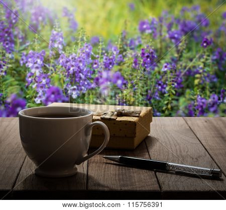Coffee, Pen And Gift Box On Wooden Table In The Garden