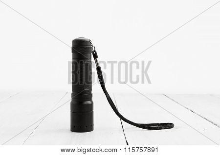 Pocket Flashlight On White Wooden Background