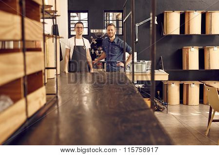 Two hipster men smiling in a modern coffee roastery
