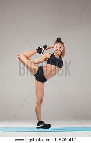 Beautiful sporty girl standing in acrobat pose or yoga asana