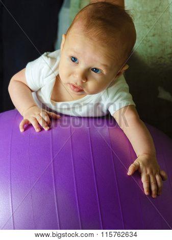 Baby Boy Is Exercising On Gymnastic Ball
