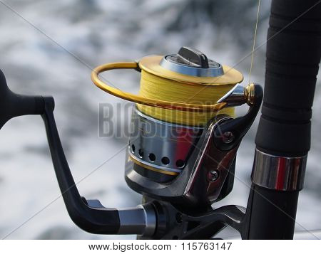 fishing-rod with spinning wheel on sea background