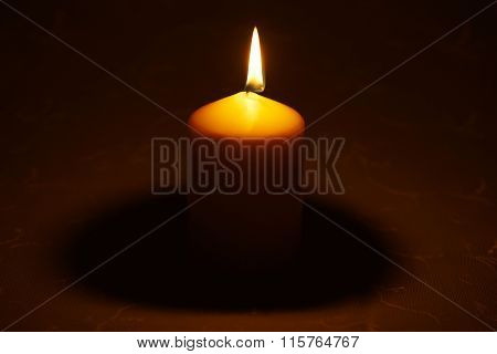 Single candle on tablecloth