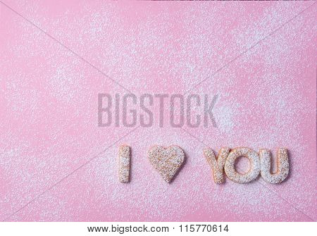 Words I Love You  Made Of Cookies Placed On A Pink Paper Surface With A Icing Sugar Poured Over