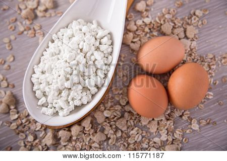 Cottage cheese, eggs on the background of scattered muesli.