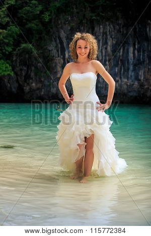 Blonde Bride In Fluffy Hands On Waist In Shallow Azure Sea