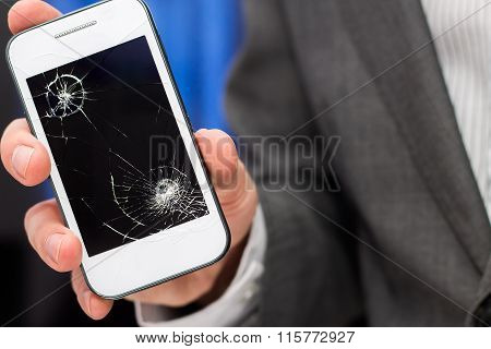Businessman shows broken smartphone with crashed screen.