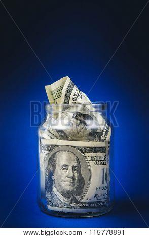 One hundred dollar bills in a glass jar. Blue background