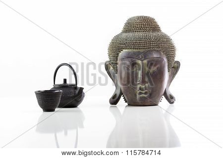 Buddha head, teapot and cup on a white background