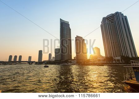 View of the skyscrapers of Bangkok with Chao Phraya river during sunset.