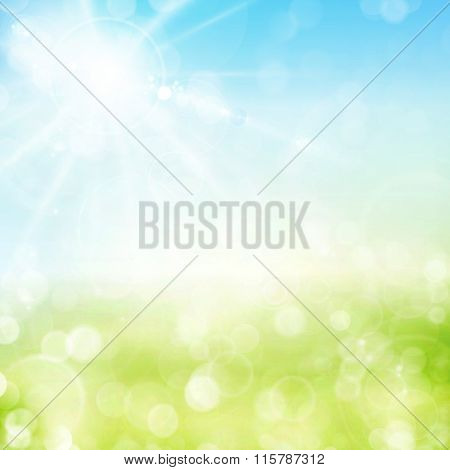 Abstract green spring background with blue sky and sun with lens flare. Blurry light dots and light