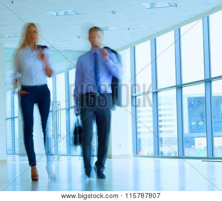 Business people walking in the corridor of an business center, blurred.