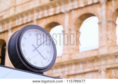 The image of clock against the Colosseum in Roma, Italy