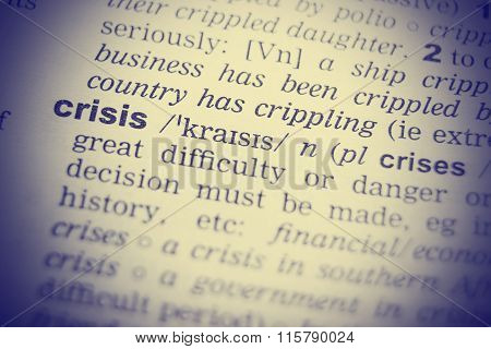Close up shot of the word crisis from a dictionary