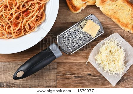 High angle view of a cheese grate with parmesan cheese on a rustic wood kitchen table . A plate of spaghetti and garlic bread are also shown.