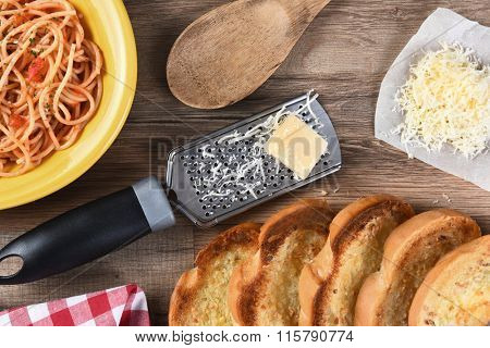 Overhead view of a kitchen table with a plate of spaghetti, garlic bread, grated parmesan cheese, a grater, wood spoon, a red checkered napkin.