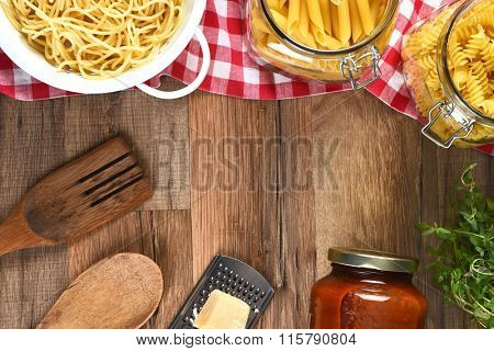 High angle view of an assortment of pastas, parmesan, cheese, grater, jar of sauce, utensil and herbs on a wood kitchen table with copy space.
