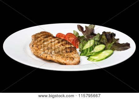Photo Of A Chicken Stake On A White Plate With A Cucumber, Tomato And A Lettuce Leaf