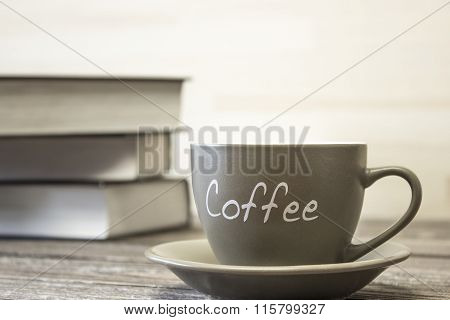 A Cup Of Coffee On The Background Of A Stack Of Books.