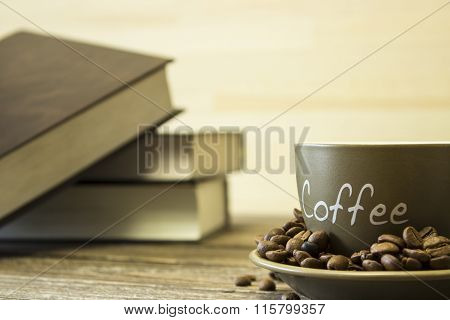 A Cup Of Coffee With Beans On The Background Of A Stack Of Books