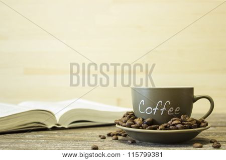 A Cup Of Coffee With Beans On The Background Of A  Book. Focus O