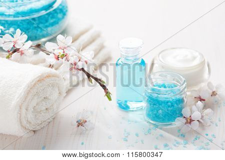 Towels , mineral bath salts, cream, shower gel, and flowers on the wooden table. Shallow DOF. Focus on the salt.