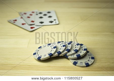 Poker Chips And Playing Cards On The Table. Focus On Chips
