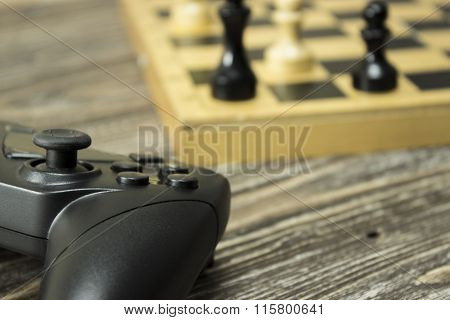 Gamepad And Chess Board With Figures On The Wooden Background. F