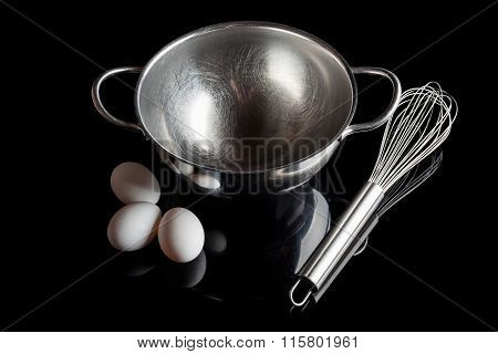 Steel bowl whisker eggs high angle with reflection on black