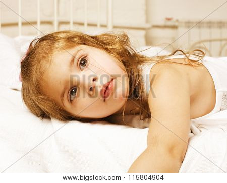 portrait of little cute girl in bed at home close up