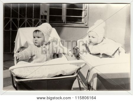 Vintage photo shows baby in a pram (baby carriege).