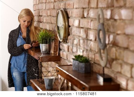 Young woman at home standing by brick wall, using mobilephone.