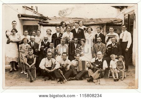 A vintage photo shows people in the back yard (during rural wedding feast), circa 1920.