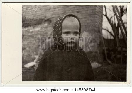 Vintage photo shows a small girl wears bandanna, circa 1942.