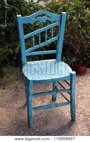 Old vintage blue chair on the ceramic floor in front of the green bushes