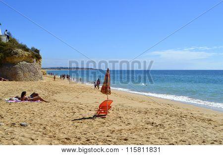 Tourists enjoying sunny weather on Armacao De Pera Beach on the Algarve coast