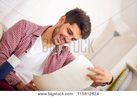 Young man sitting on the sofa and holding in his hand university degree