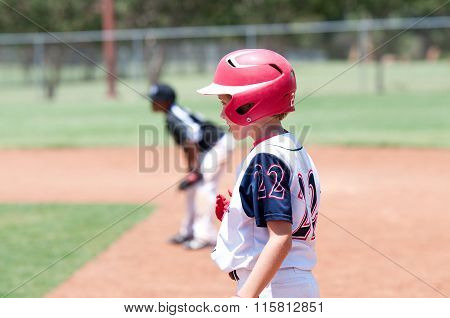 Young American Baseball Boy standing On First Base