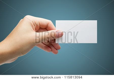 Hand holding white blank business visit card, gift, ticket, pass, present isolated on blue backgroun