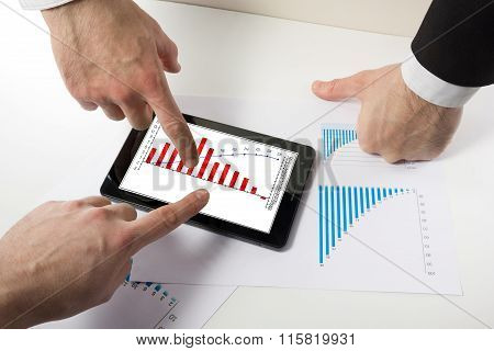 Business people on a meeting analyzing financial reports discuss