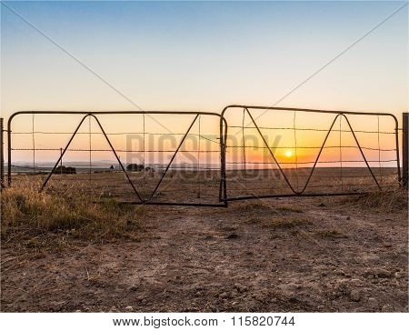 Sunset through a farm gate.