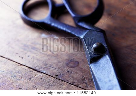 Vintage scissors on a wooden work table. Shallow depth of field. low key.