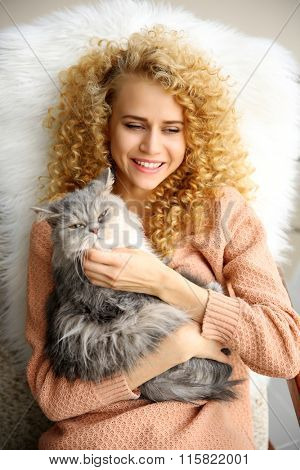 Young woman and cat lying on bed in the room